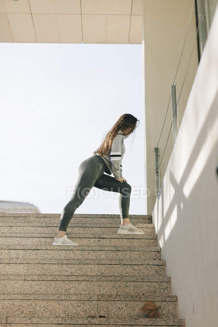 Young woman in sportswear training at street — Stock Photo