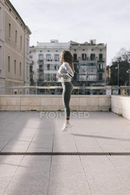 Девушка в спортивной одежде тренируется на улице — стоковое фото