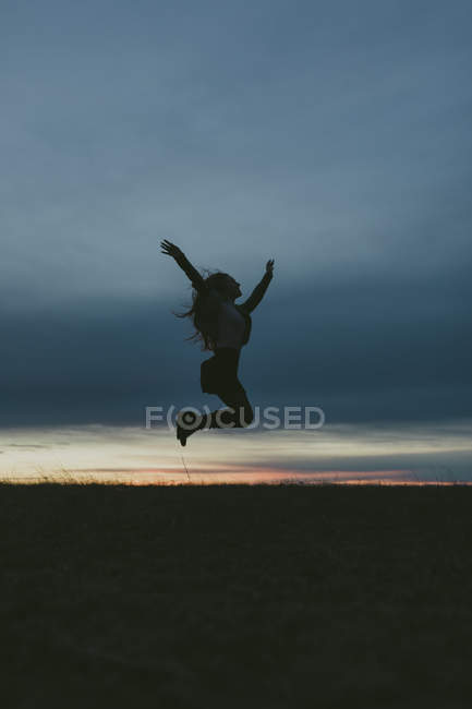 Silhouette of woman against blue sky at sunset, selective focus — Stock Photo