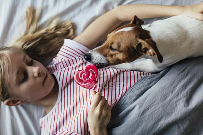 Mädchen isst rosa Lutscher in der Nähe von niedlichen Hund zu Hause, selektiver Fokus — Stockfoto