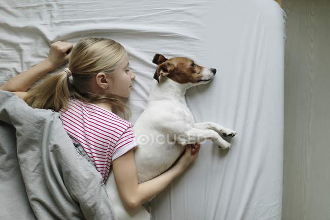 Vista elevada de menina com cachorro fofo na cama — Fotografia de Stock