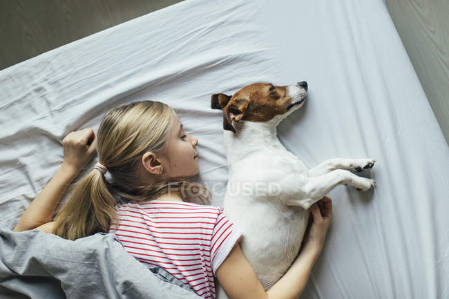 Vista elevata della ragazza con cane carino sul letto — Foto stock