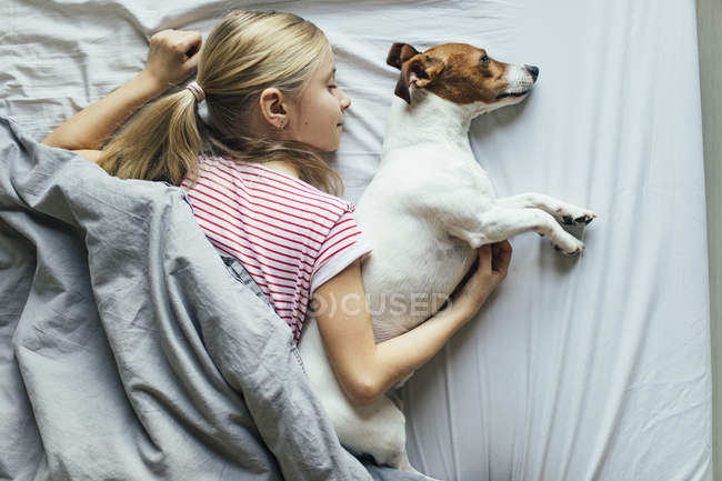 Elevated view of girl with cute dog on bed — Stock Photo