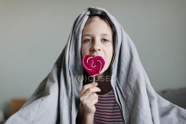 Fille manger sucette colorée sur le lit, mise au point sélective — Photo de stock