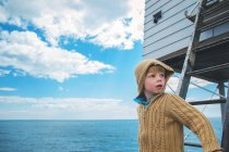 Boy standing on ladder and looking at away — Stock Photo