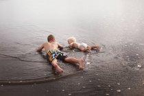 Братья, лежа в воде — стоковое фото
