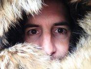 Man peering through fur hood — Stock Photo
