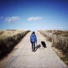 Garoto andando com cachorro — Fotografia de Stock