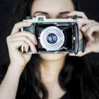 Mujer con la vieja cámara contra la cara - foto de stock