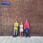 Bambini in piedi davanti al muro di mattoni — Foto stock