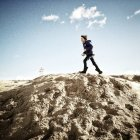 Boy running on sand dune — Stock Photo