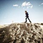 Garçon courant sur une dune de sable — Photo de stock