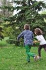 Niño y niña saltando - foto de stock