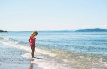 Cute girl standing by sea — Stock Photo