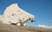 Молодая женщина, восхождение на большой камень — стоковое фото