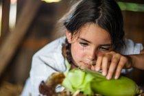 Girl husking corn — Stock Photo