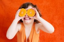 Girl holding oranges in front of eyes — Stock Photo