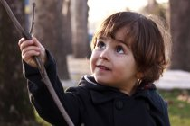 Boy with stick in park — Stock Photo