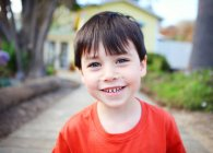 Little boy smiling at camera in park — Stock Photo