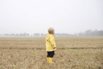 Boy in field in rainwear — Stock Photo