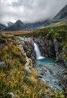 Cachoeira durante dia enevoado nas montanhas — Fotografia de Stock
