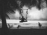Silhouette of boy on swing — Stock Photo