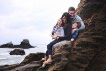 Семья, сидящая на камнях — стоковое фото