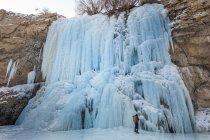 Routard debout sous la cascade gelée — Photo de stock