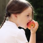 Girl eating apple — Photo de stock