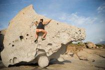 Donna arrampicata su grande roccia singola — Foto stock