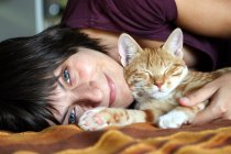 Woman lying on bed with kitten — Stock Photo