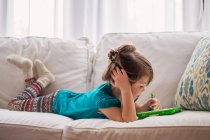 Girl playing with digital tablet — Stock Photo