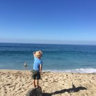 Junge steht auf Felsen am Strand — Stockfoto