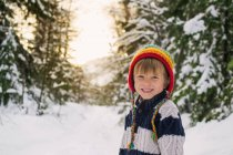 Smiling boy standing in snow — Stock Photo