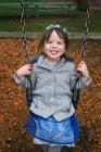 Smiling girl on swing — Stock Photo