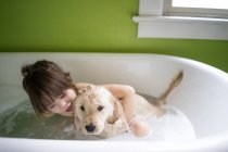 Girl sitting in bath with puppy dog — Stock Photo