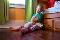 Boy sitting on floor with dog — Stock Photo
