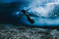 Femelle, nageant sous les vagues — Photo de stock
