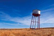 Torre de água inclinada em campo — Fotografia de Stock