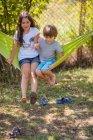 Мальчик и девочка сидят на гамаке — стоковое фото