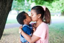 Woman giving her son a kiss in the park — Stock Photo