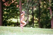 Girl jumping in sprinkler — Stock Photo