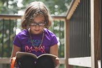 Livre de lecture fille sur balcon — Photo de stock