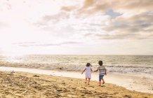 Giovane ragazzo e ragazza a piedi sulla spiaggia — Foto stock