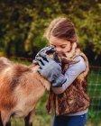 Girl kissing goat — Stock Photo