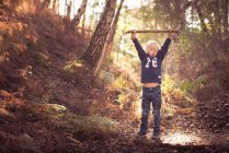 Boy with stick in forest — Stock Photo