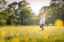 Young boy playing in meadow — Stock Photo