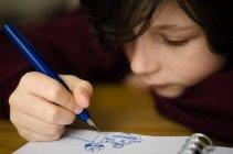 Хлопчик малювання в блокнот — стокове фото