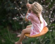 Young girl sitting on swing — Stock Photo