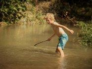 Boy in stream holding stick — Stock Photo